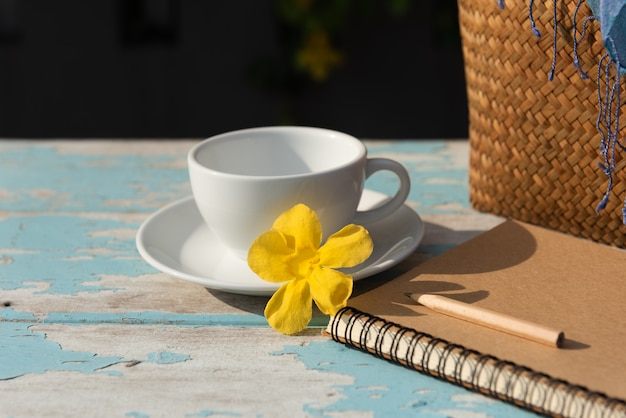 Coffee cup on wood table with brown memo notebook