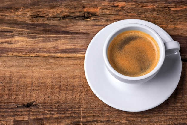 Coffee cup on a wooden table. dark background.