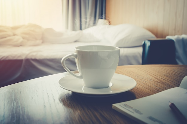 Coffee cup on wooden table morning time coffee in the bed room for wake up life- warm vint