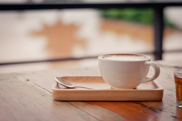 Coffee cup on wooden table surface background vintage style selective focus with copy space.