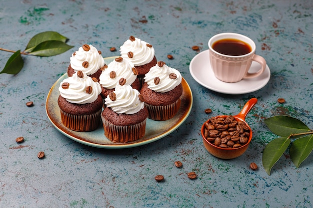 Coffee cupcakes decorated with whipped cream and coffee beans.