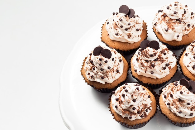 Coffee cupcakes with mocha buttercream and chocolate decorations on a white table