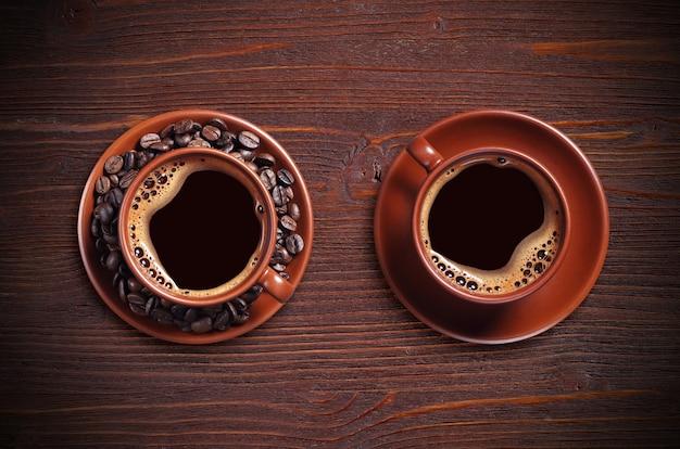 Кофейные чашки и бобы на деревянном столе