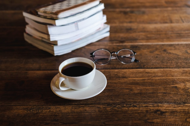 Coffee cups and books placed on old wooden tables