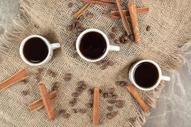 Coffee cups, cinnamon sticks and coffee beans on burlap