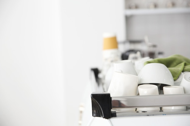 Coffee cups on coffee machine in white coffeeshop