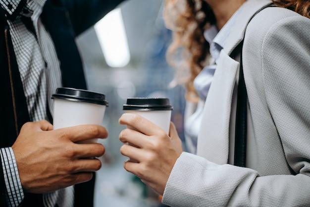 愛するカップルの手にコーヒーカップ