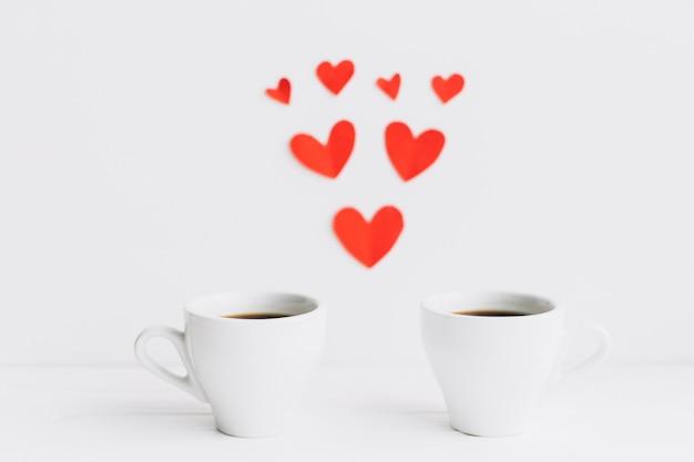 Tazze di caffè vicino alla composizione di cuori di carta