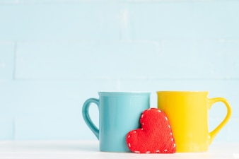 Coffee cups on wooden table with handmade red heart. Friendship day concept
