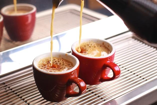 Coffee cups stand inside the coffee machine on a grid, fresh coffee is poured inside the cups