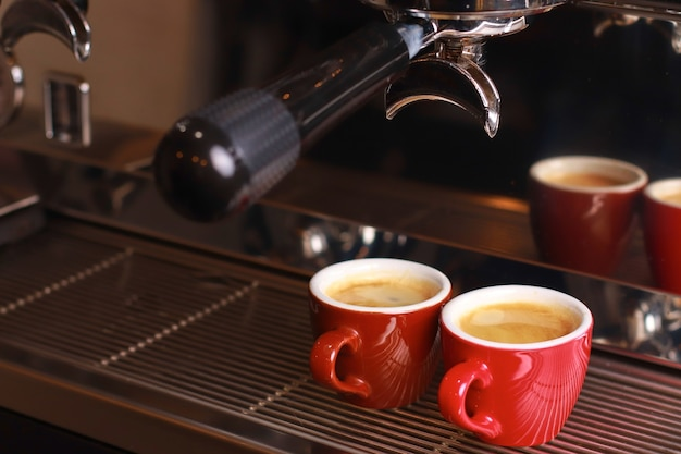 Чашки для кофе стоят внутри кофемашины на решетке, внутрь чашек наливается свежий кофе.