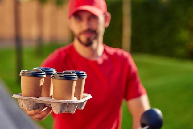 Чашки кофе, стоя на доске доставки в руке курьера человека на открытом воздухе. выборочный фокус. концепция доставки еды