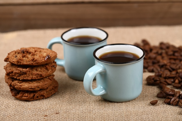 Coffee cups with beans and cookies. side view.