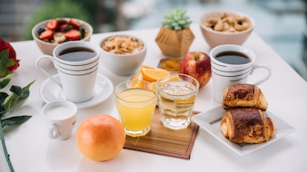 Coffee cups with sweet buns and juice on table