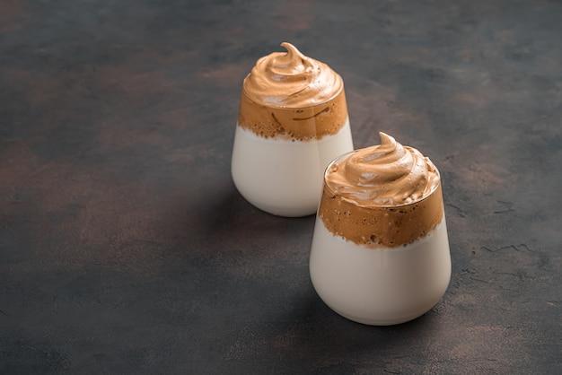 Кофейный десерт с молоком в двух стаканах на коричневой стене. вид сбоку, копия пространства.