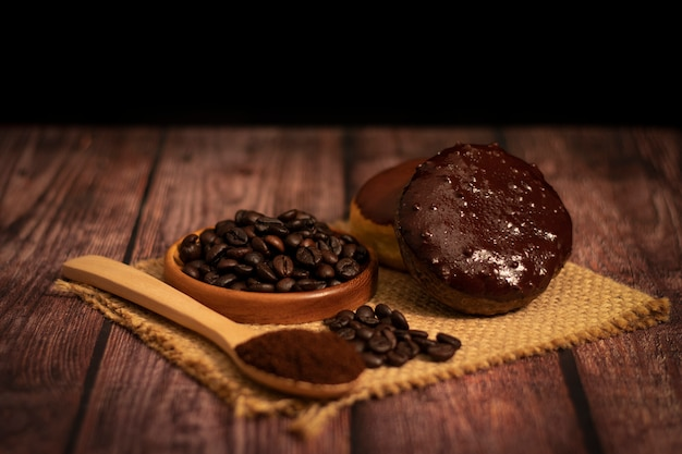 Coffee donut with organic coffee beans and coffee powder on wooden spoon on the wooden table