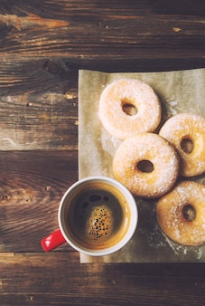 Coffee and donuts sprinkled with icing sugar on rustic wooden surface. vintage toned picture. top view.