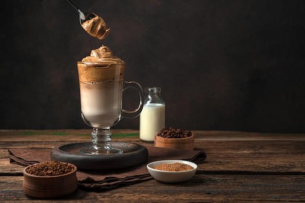 材料が入った茶色の壁にコーヒーの飲み物とスプーンとコーヒーの泡。爽快で清涼感のあるドリンク。側面図、コピー スペース。
