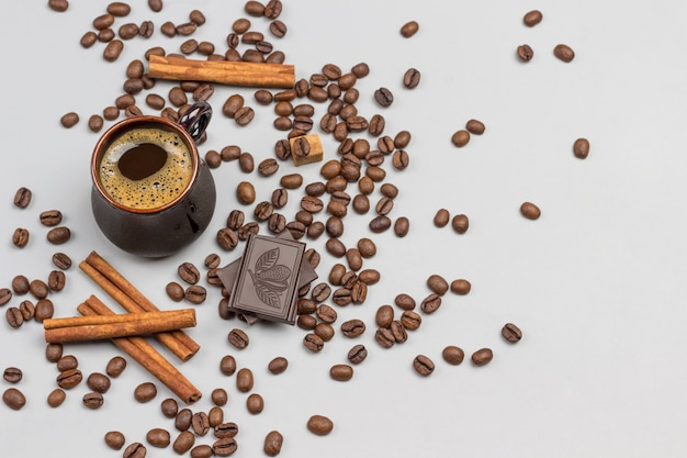 Coffee drink in black cup. cinnamon sticks, pieces of chocolate and coffee grains on table. gray background. top view