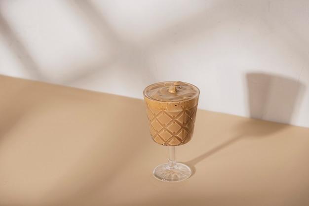 夏の太陽の影とベージュと白のニュートラルな背景に茎のガラスでコーヒーを飲みます。コピースペースのある背景
