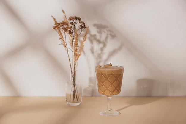 여름 태양에서 그림자와 베이지 색과 흰색 중립 배경에 말린 된 꽃의 부케와 함께 형태소 유리에 커피 음료. 복사 공간 배경