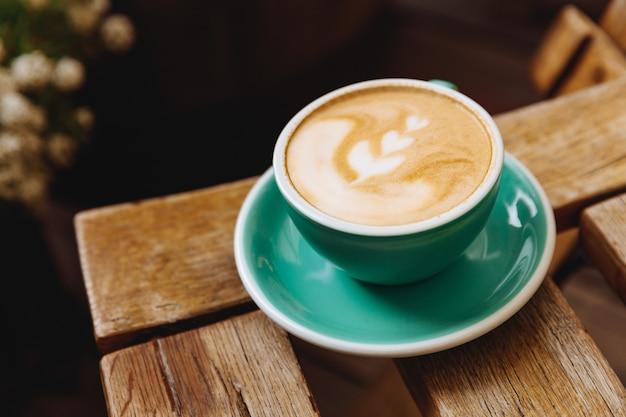 Кофейный напиток с красивым латте-артом сверху в керамической чашке зелени с блюдцем на деревянном столе с размытым фоном