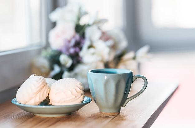 Кофейный напиток с маршмеллоу на окне утром