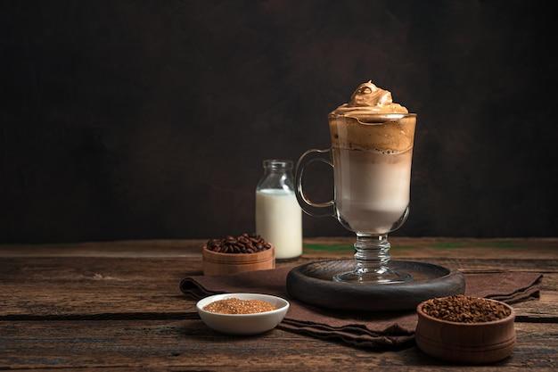 コピーするスペースのある茶色の壁に、ミルク、氷、ホイップ フォームを入れたコーヒー ドリンク。ダルゴナコーヒー。