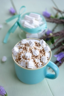 Coffee drink with whipped foam and marshmallows on a light azure.