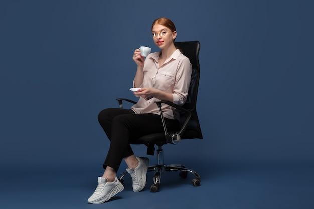 커피 마시기. 파란색 스튜디오 벽에 평상복을 입은 젊은 여성