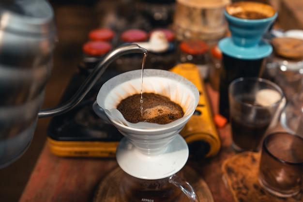 커피 드립, 주전자에서 뜨거운 물로 커피를 따르십시오.