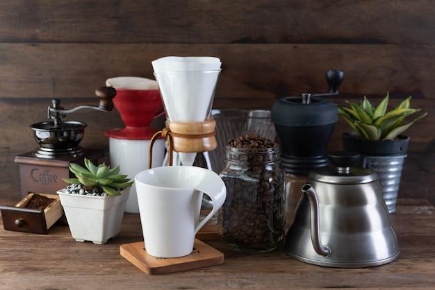 コーヒードリップセット、ロースト豆、やかん、グラインダー、白いカップ、フラワーポット、木製のテーブルと背景