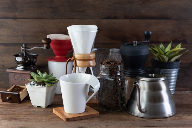 Coffee drip set with, roasted beans, kettle, grinder, white cup and flower pot on wood table and background