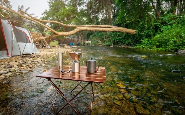 自然公園の川の近くでキャンプしながらコーヒーを点滴
