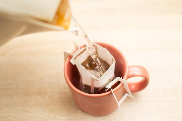 뜨거운 물을 붓는 종이 필터 백에 담긴 대체 추출 특수 커피 컵에 커피 드립