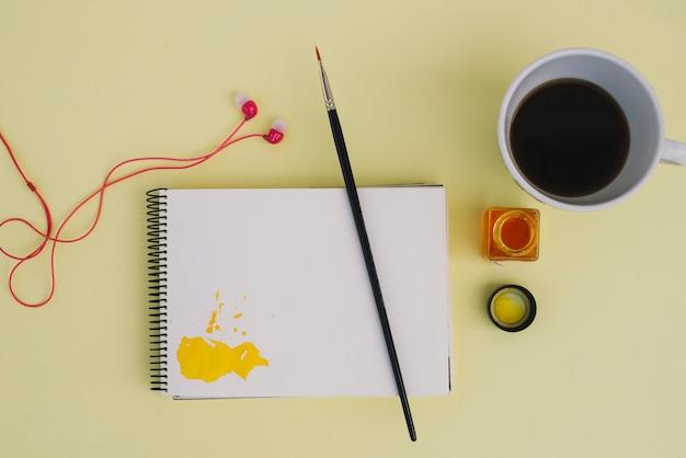 Coffee and earphone near painting stuff