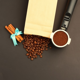 Coffee espresso in a holder, coffee-beans, rolls of cinnamon