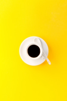 Coffee espresso in small white ceramic cup on yellow vibrant background. Minimalism Food Morning Energy Concept.