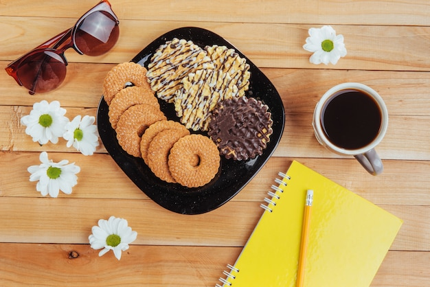 Coffee espresso stands on a wooden table with cookies, pad and pencil.