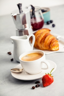 Coffee espresso in white cup with milk, jam and croissants.