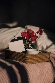 Кофейные цветы и открытка на подносе на кровати