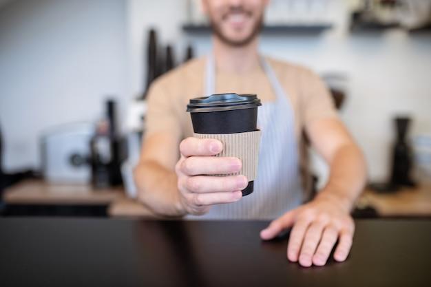 Кофе для тебя. бумажный стаканчик кофе с крышкой в протянутой руке бариста, стоящего за барной стойкой в кафе