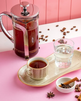 Caffè in frech stampa bicchiere d'acqua e chicchi di caffè sul tavolo