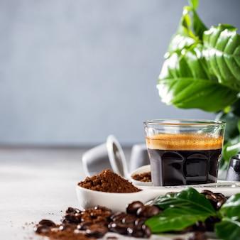 豆と葉を添えたガラスのコップで淹れたてのコーヒー。コピースペースのある食品飲料表面