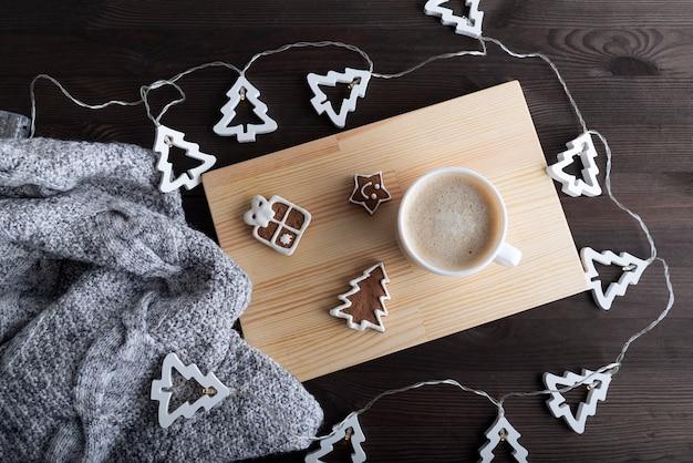 コーヒー、ジンジャーブレッド、クリスマスガーランド、暖かい毛布。上面図。正月フラットレイ。