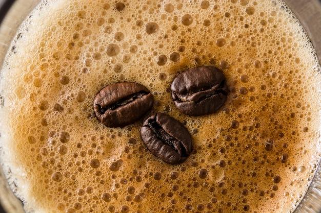 Кофейный стакан и кофейное зерно на деревянном столе крупным планом
