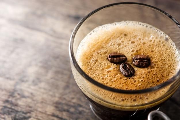 Кофейный стакан и зерно кофе на деревянный стол копией пространства