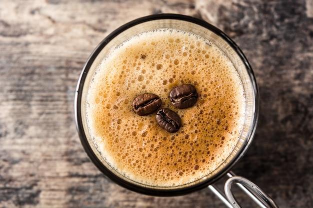 Кофейный стакан и кофейное зерно на деревянном столе