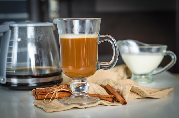 Coffee in a glass cup and cinnamon on the table