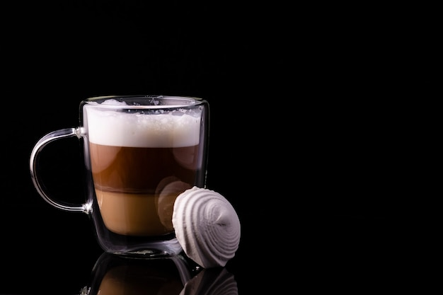 Coffee in a glass cup and marshmallows placed against the cup.